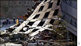 Several workers congregate near the collapsed facade of World Trade Center Building 7