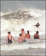 [ image: Swimmers brave the huge waves generated by the wind]