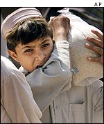 A boy carries a sack of rice