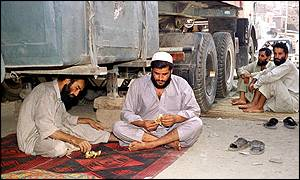 Afghan truck drivers sitting idle