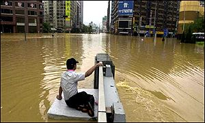 A Taiwanese man looks at a Taipei street while sitting on a floating rubber cushion