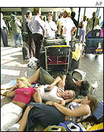Air travellers lie down as they queue