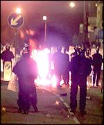 Riot police face an angry crowd in Oldham