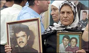 Palestinian woman holds photos of family members killed in the Beirut refugee camps