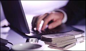 A man counts dollar bills while using a laptop