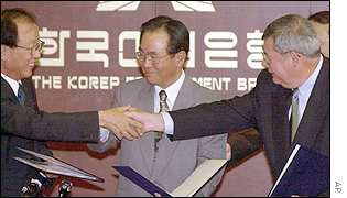 Rudy Schlais of GM right shakes hands with Lee Jong-dae, Daewoo Motor Chairman, left, as KDB governor Jung Keun-young looks on