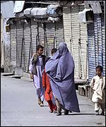 A woman and children walk past shuttered shops in Quetta