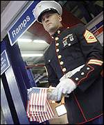 A marine hands out stars and stripes flags