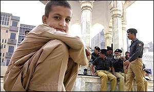 A boy sits by soldiers in Peshawar in Pakistan