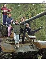 Ethnic Albanian children pose on knocked-out Macedonian tank