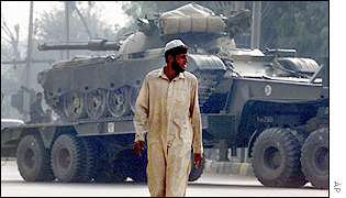 Pakistani man in front of tank