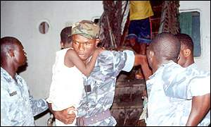 A soldier carrying a child out of slave vessel in Benin in April