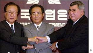 Daewoo and GM executives shake hands as the US giant takes over parts of the bankrupt car maker