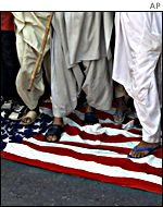 Demonstrators walk on an American flag during a protest in Karachi