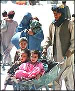 Refugee with children in wheelbarrow