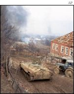 A Russian tank rolls through a Chechen village