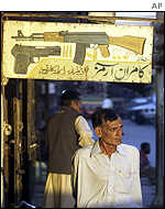 A man walks past an arms dealer in Quetta