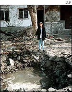 A woman views the rubble in Grozny