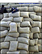 A man rests on bags of grain in a UNHCR warehouse