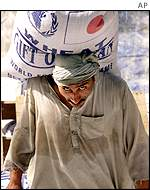 A Pakistani man hefts a bag of rice donated by Japan