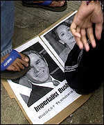 Protester treads on picture of Presidents Arroyo and Bush