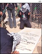 Fatah activists pray over the tomb of  a Palestinian killed by Israeli forces