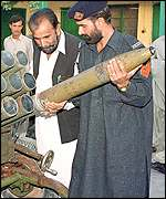Pakistani policeman displays multi-barrelled rocket launcher seized on border
