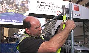 Man putting up steel fence by conference centre