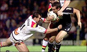 Bradford's Daniel Gartner and Jamie Peacock tackle Wigan's Matthew Johns