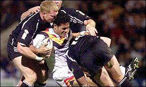 Bradford's Tevita Vaikona is brought down by Wigan's Neil Cowie and David Furner
