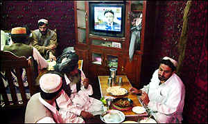 Afghan refugees in Pakistan eat dinner as President Musharraf speaks on a TV behind them