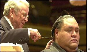 US Ambassador Howard Baker uses a scissors to cut part of Akebono's topknot
