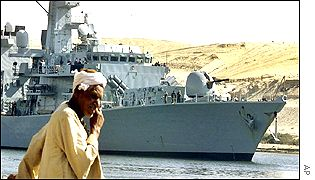 An Egyptian fisherman watches the British frigate Monmouth pass through the Suez Canal on its way to join a task force of British ships assembling for war games off Oman