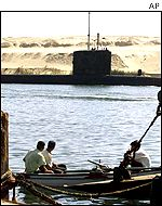 Egyptian fishermen watch a submarine on its way to join British ships for war games off Oman