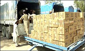 Workers load a shipment of UN World Food Programme food aid for Afghanistan at the Peshawar airport