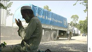 An Afghan prays in front of a  WFP truck in Peshawar