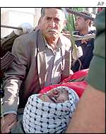 A Palestinian man sits beside the body of his son during the funerals of four policemen