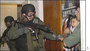 An armed agent points a gun in the direction of Elian Gonzales