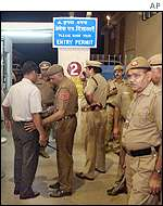 Delhi police officer frisks airport employee