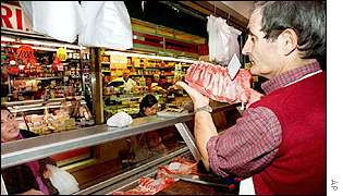 Butcher in traditional shop in Rome serves customer