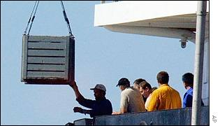 A box containing bodies is hoisted onto a ship