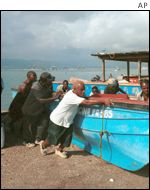 Jamaican fishermen pushing boats up beach