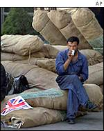 Airport worker relaxes after unloading a UK aid shipment from Britain to northeast Iran, which neighbours Afghanistan