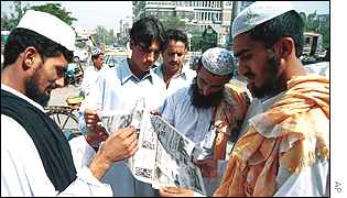 Pakistani men read news of the air strikes