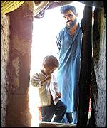 An Afghan boy and his father stand in the doorway of their tent in a refugee camp in south-eastern Iran