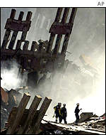Firefighters walk among the smouldering ruins of the World Trade Center
