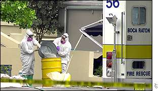 FBI agents wearing bio-hazard suits pour liquid into a yellow drum