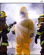 A hazardous materials team member is hosed down after investigating the incident