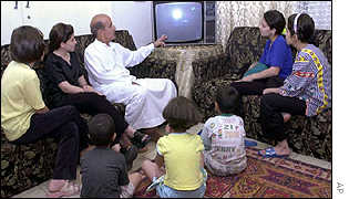 An Iraqi family watches the US strikes on Afghanistan on television