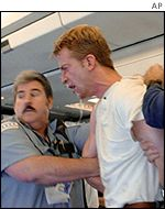 Edward Coburn, 31, is held by unidentified passengers on an American Airlines flight